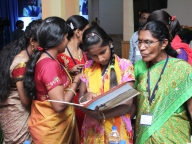 Adolescent girl leader and outreach worker from Samata go through the conference kit