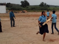 Girls and boys playing cricket in mixed teams.