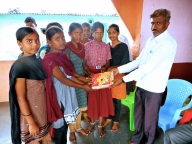 School Development & Monitoring Committee member distributes notebooks to girls as part of IDGC in Bijapur